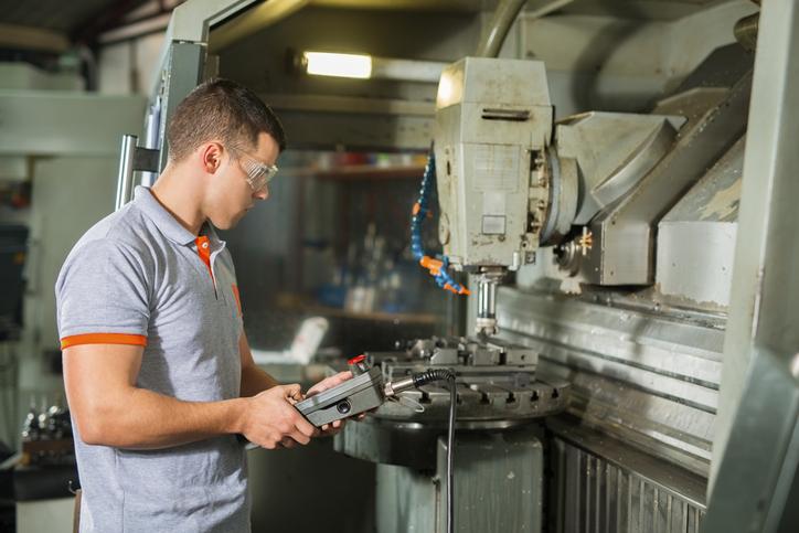 Homem operando máquina de usinagem