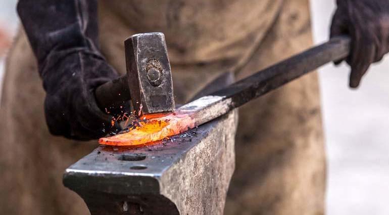 Ferreiro forjando aço.